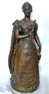 Bronskleurig beeld van Wilhelmina in haar inhuldigings kleding