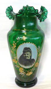 Onderdeel van een driedelig smaragd groene glazen kaststel gemaakt in 1890 na het overlijden van Koning Willem III. Koningin Emma werd Regentes. Hier afgebeeld in rouwkleding.