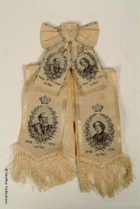van zijde gemaakte sjerp met portretten van Koning Willem III en Koningin Sophie t.g.v hun zilveren regeringsjubileum in 1874